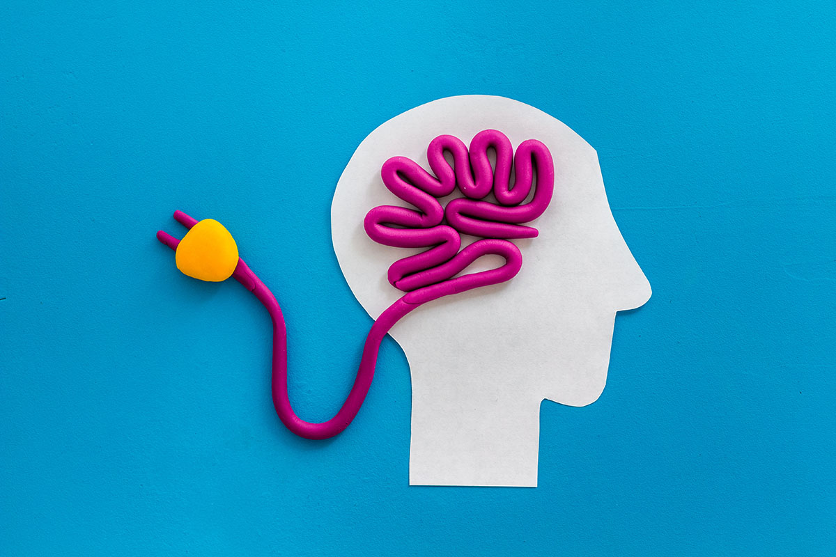Brain charging and mental rest. Plug and cable leads to plastiline meanders on blue background top view, ©9dreamstudio / AdobeStock