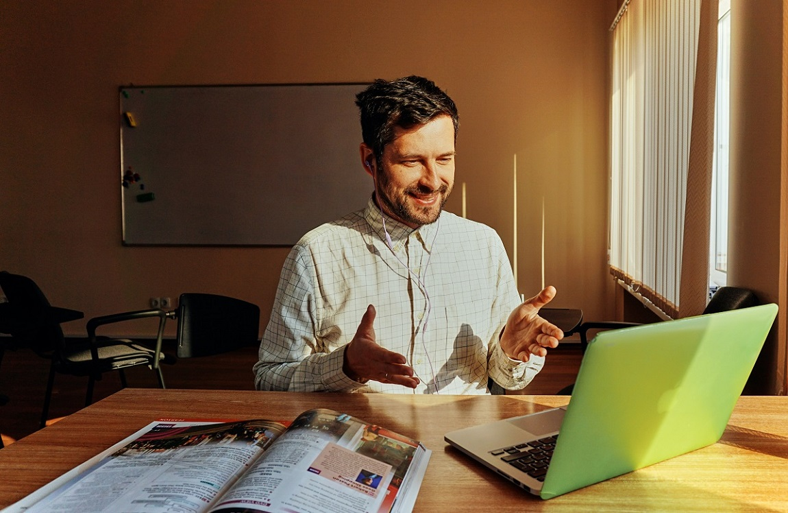 Photo of a man looking at a computer with his hands in the air indicating that he is talking.