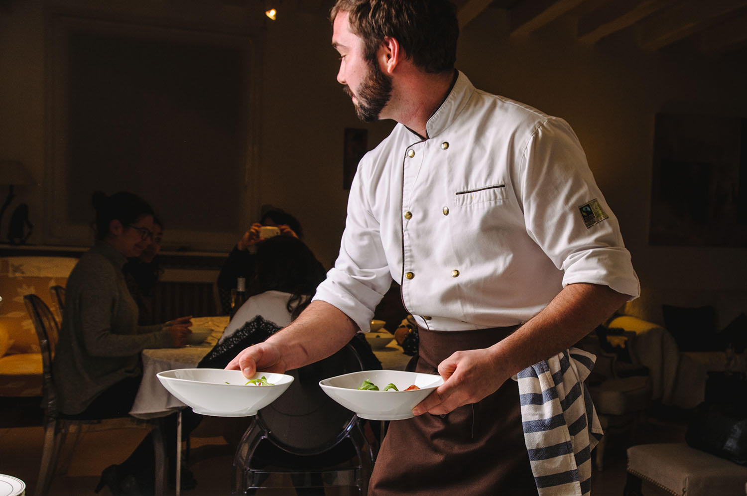 Professional chef serving dishes in a guest's home. © La Belle Assiette