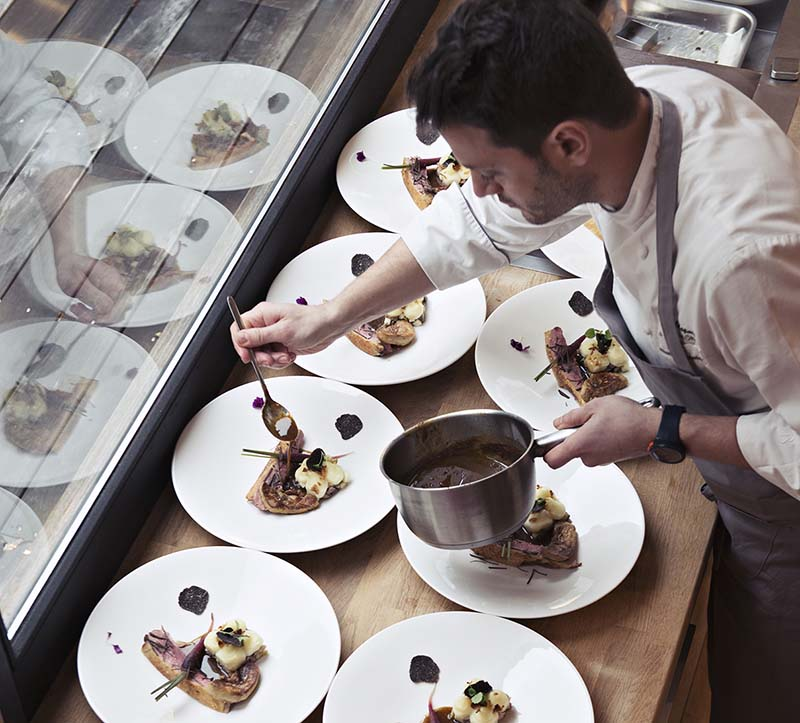 Professional chef plating dishes in a guest's home. © La Belle Assiette