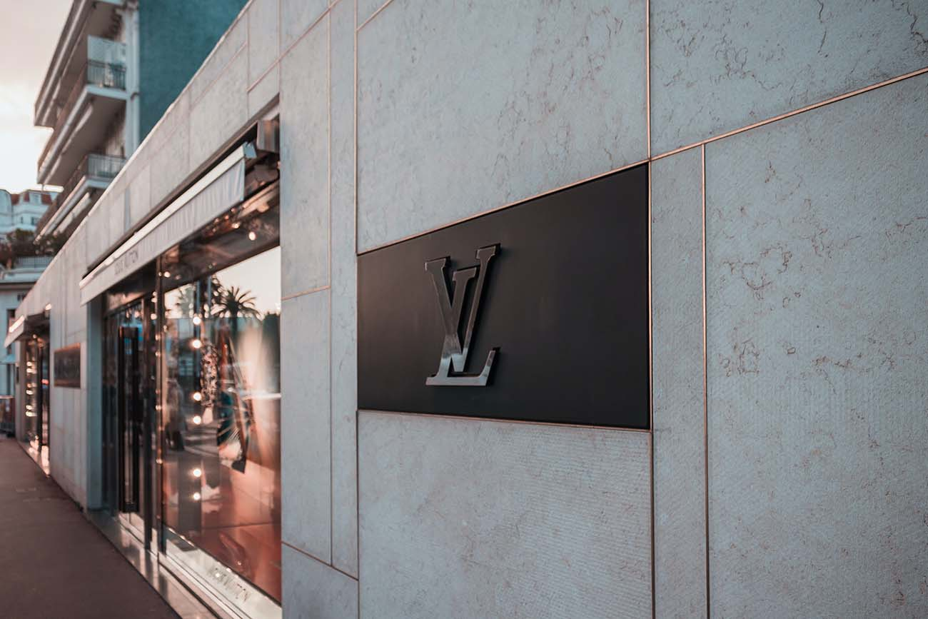 Feature photo by Jannis Lucas/Unsplash. Photo of Louis Vuitton logo outside a store.