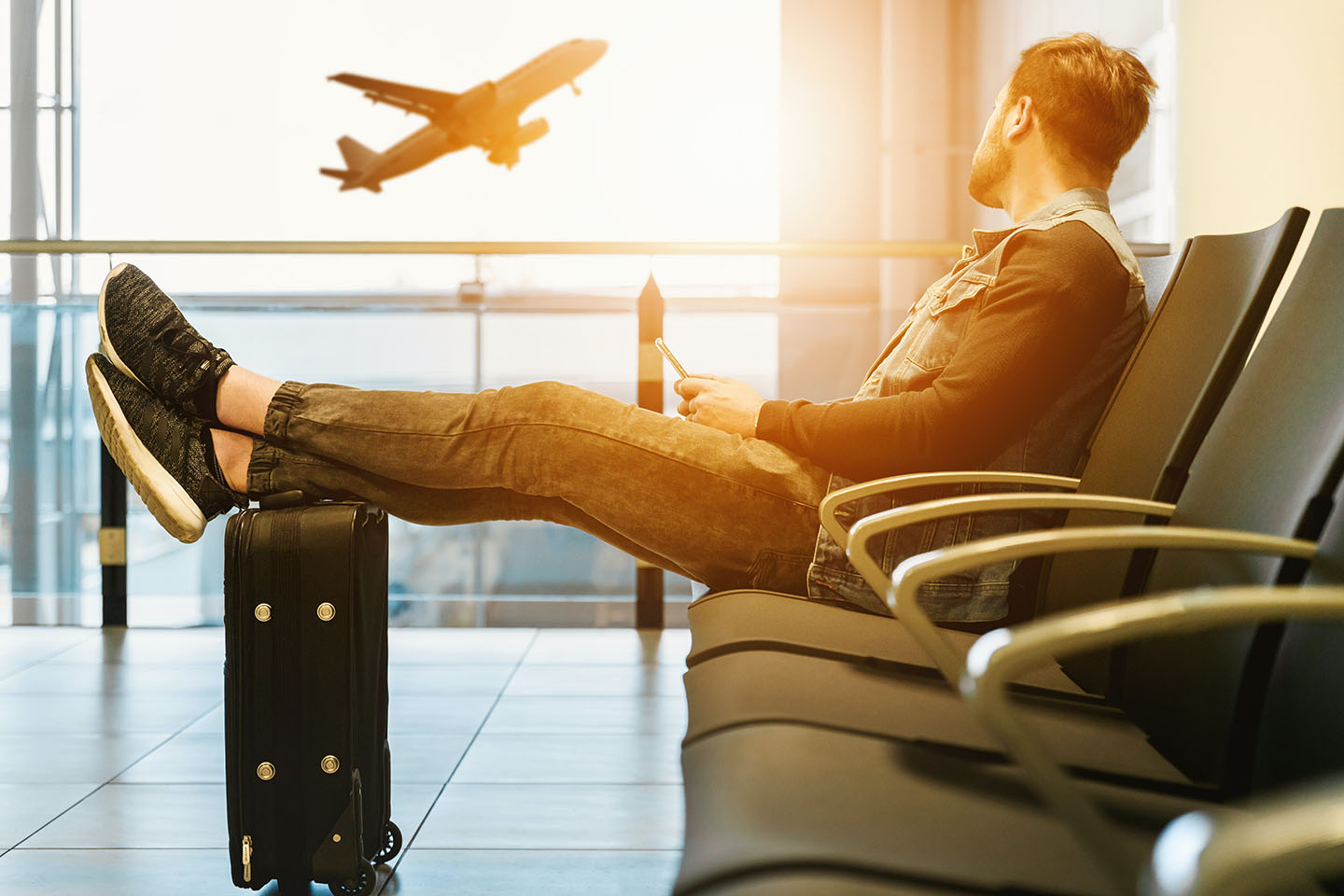 Man sitting on gang chair with feet on luggage looking at airplane,