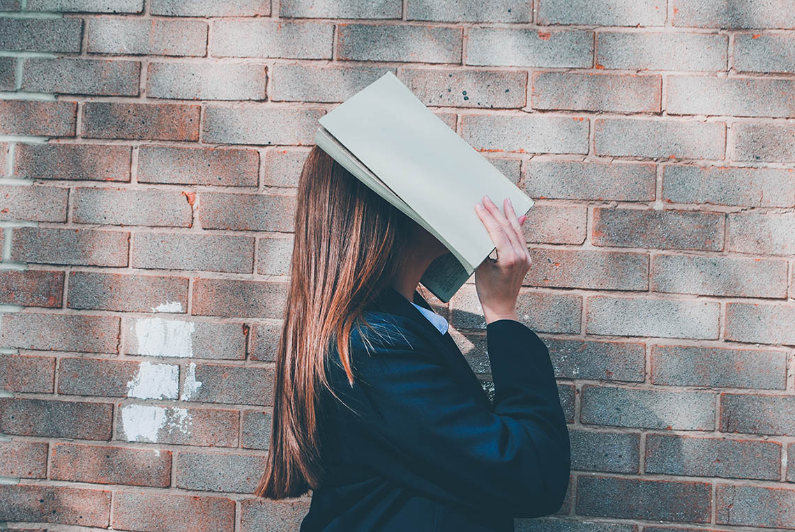 Woman covering her face with an open book, © Siora Photography / Unsplash