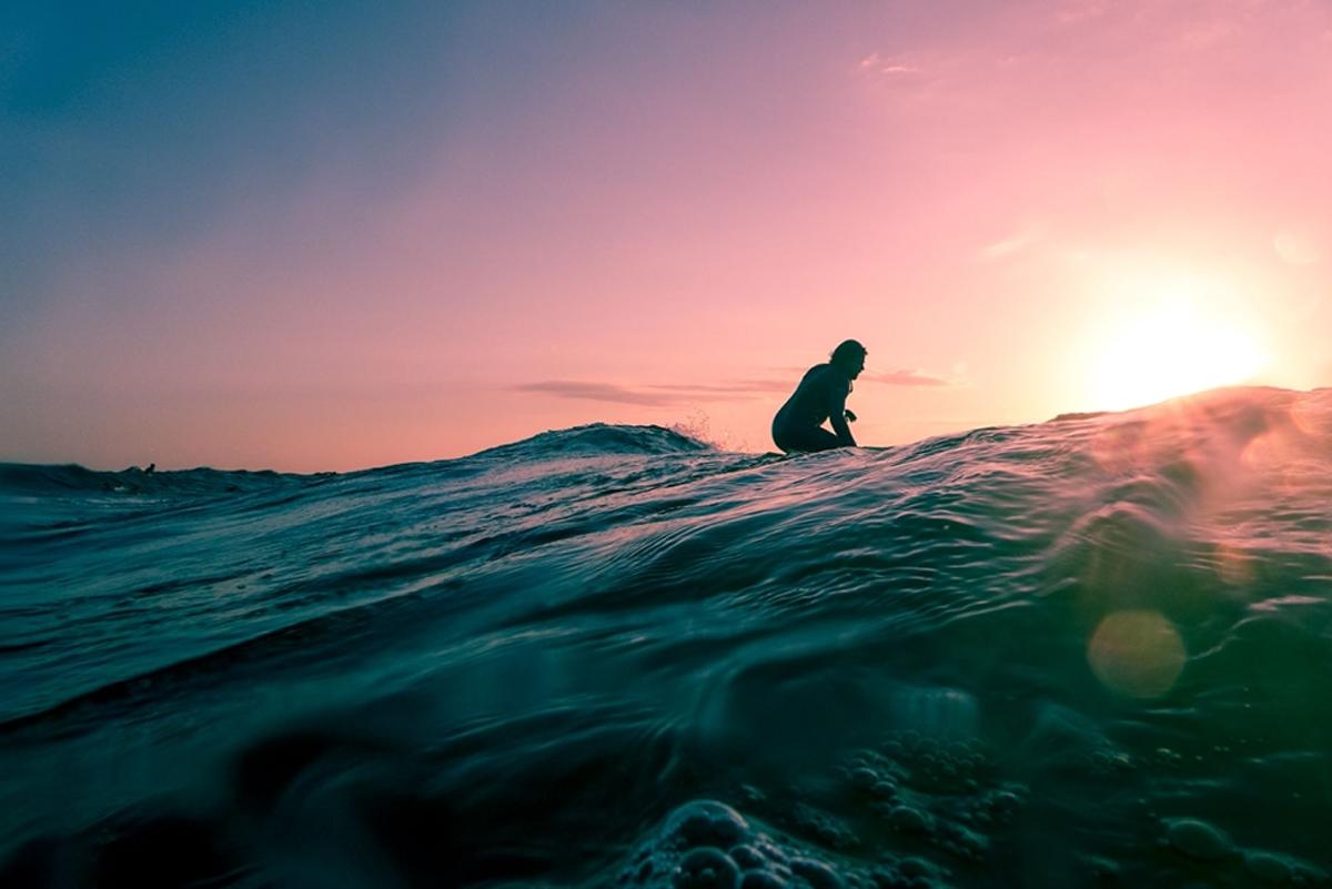 Man surfing on ocean water during golden hour, © Linus Nylund / Unspash