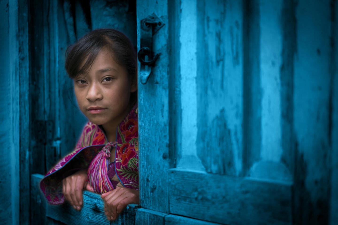 Young poor girl looking out of a window